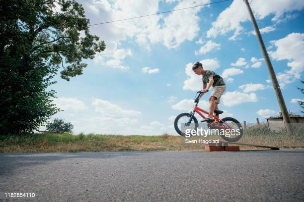 boy riding bicycle off ramp - play off stock pictures, royalty-free photos & images