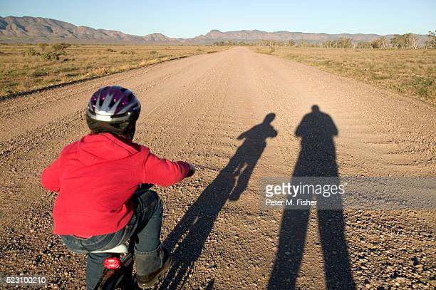 Boy Riding Bicycle on Dirt Road