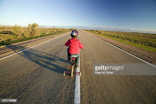 Boy Riding Bicycle on Empty Highway