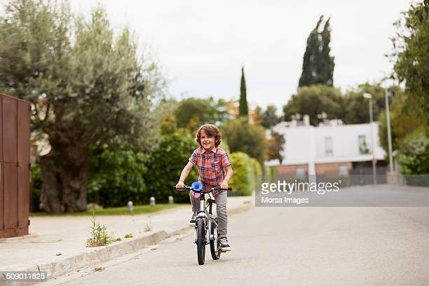 Boy riding bicycle on street