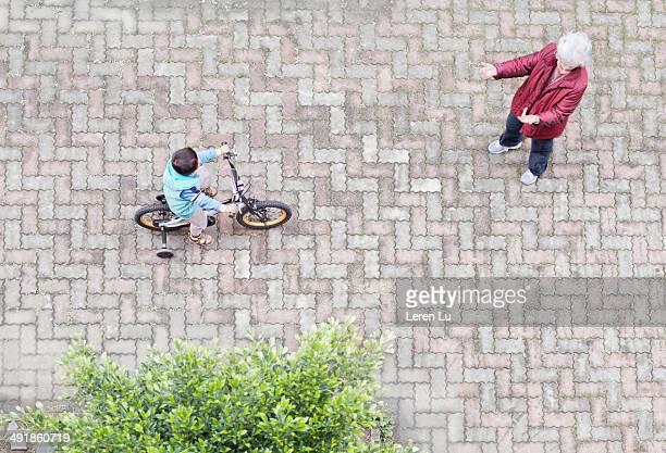 Boy riding bicycle toward grandmother.