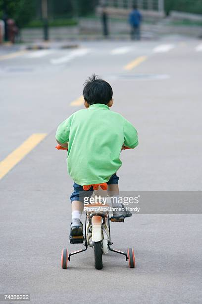 Boy riding bicycle with training wheels, rear view