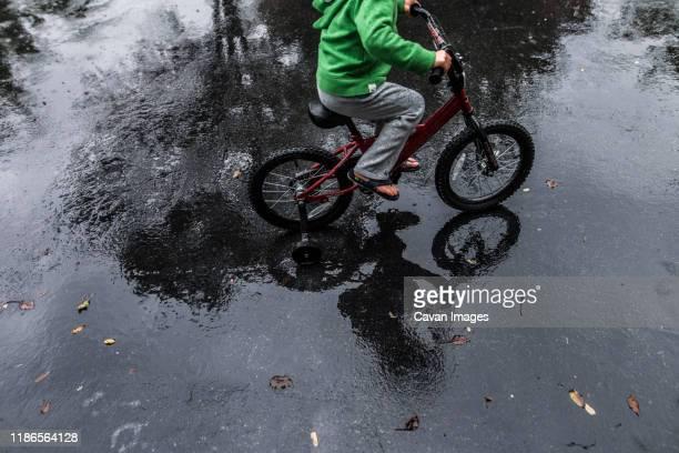 boy riding bike through driveway puddle with flip flops on - ein junge allein stock-fotos und bilder