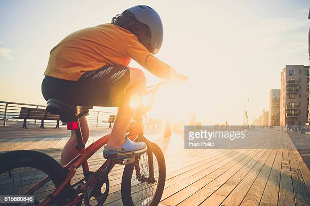 Boy riding his bike on the boardwalk.