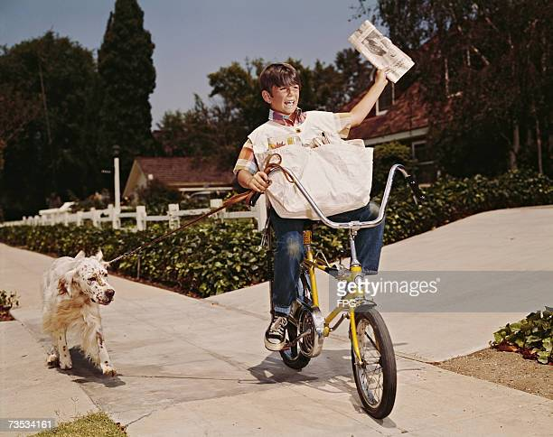 A boy riding his bike while delivering papers with his dog in tow 1970s