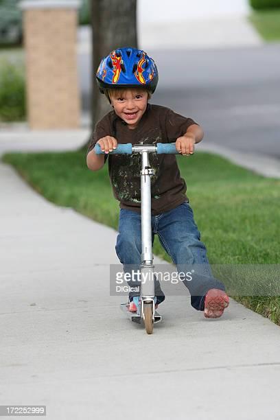 Junge auf seinem Scooter