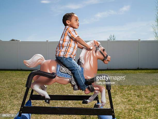 boy riding hobby horse toy in back yard - idaho falls stock photos and pictures