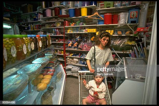 Boy riding in shopping cart manned by his mother passing olivestopped cheese case framed by household products section at supermarket in Damascus...