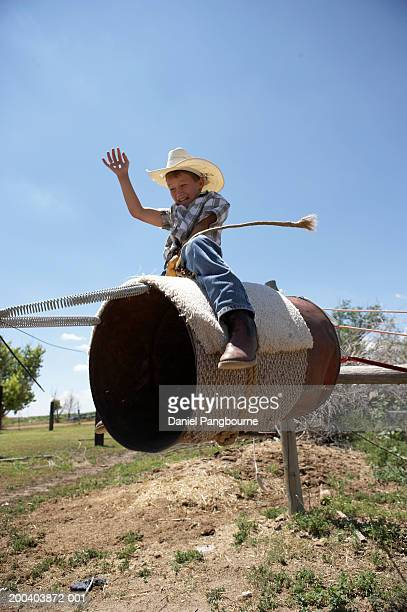 Boy (8-10) riding makeshift rodeo bull