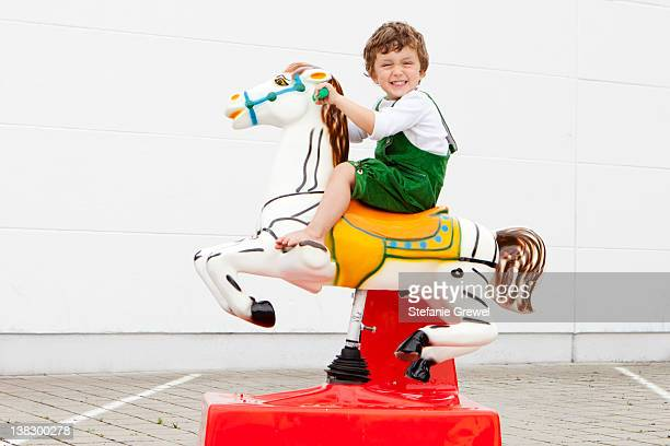 boy riding mechanical horse outdoors - riding stock pictures, royalty-free photos & images