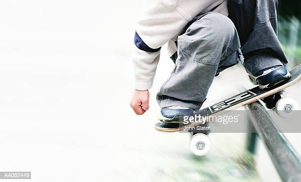 Boy (6-8) riding metal rail with skateboard, low section
