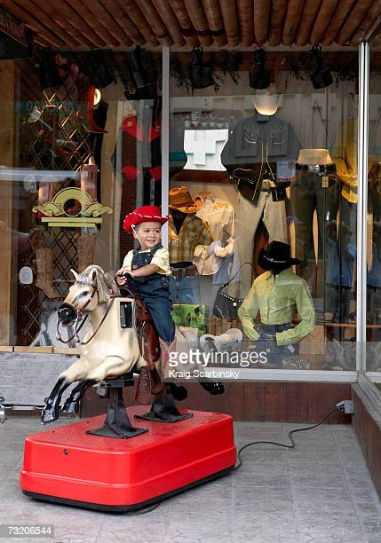 Boy (2-4) riding on coin operated horse outside store