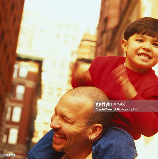 boy (4 years) riding on father's back, drumming - 30 39 years imagens e fotografias de stock