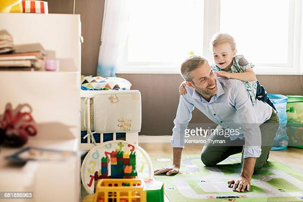 boy riding on fathers back while playing at home - riding stock photos and pictures