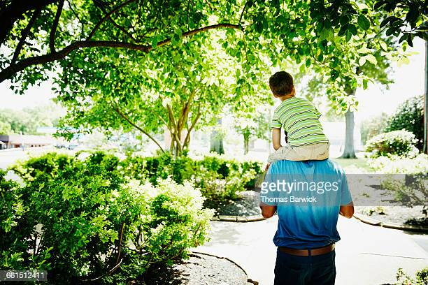 boy riding on fathers shoulder - carrying a person on shoulders stock photos and pictures