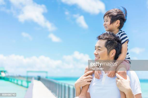 boy riding on father's shoulders - carrying a person on shoulders stock photos and pictures