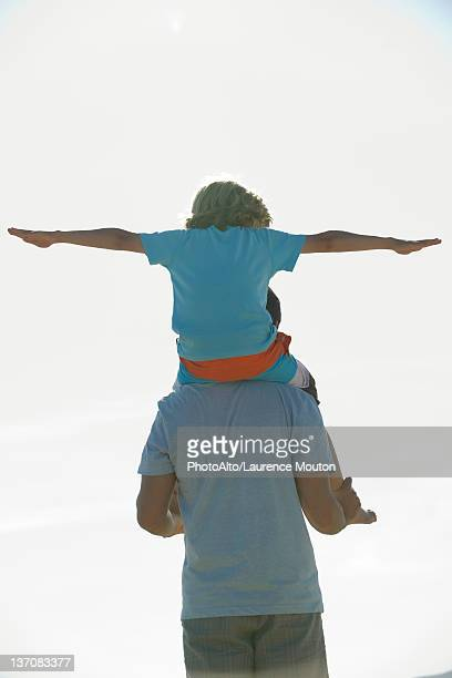 Boy riding on father's shoulders, rear view