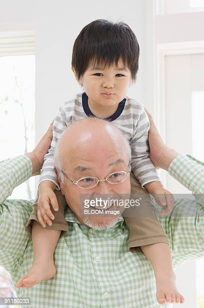 Boy riding on grandfather's shoulders