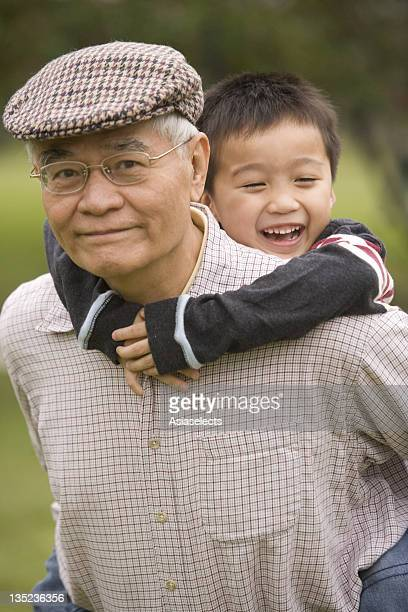 boy riding piggyback on his grandfather - flat cap stock photos and pictures