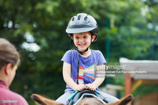 boy riding pony in urban farm - compassionate eye foundation stock pictures, royalty-free photos & images