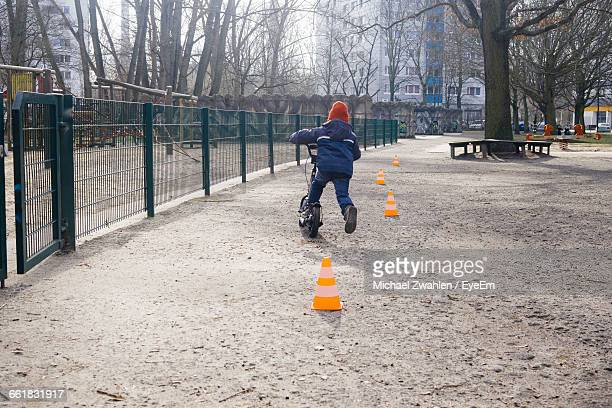 boy riding scooter at park on sunny day - traffic cone stock pictures, royalty-free photos & images