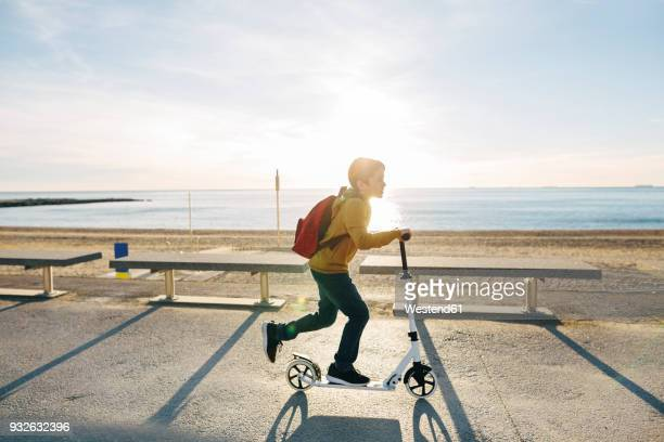 boy riding scooter on beach promenade at sunset - scooter stock pictures, royalty-free photos & images