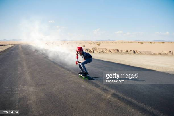 Boy riding skateboard propelled by fire extinguisher