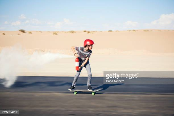 boy riding skateboard propelled by fire extinguisher - horizon over land stockfoto's en -beelden