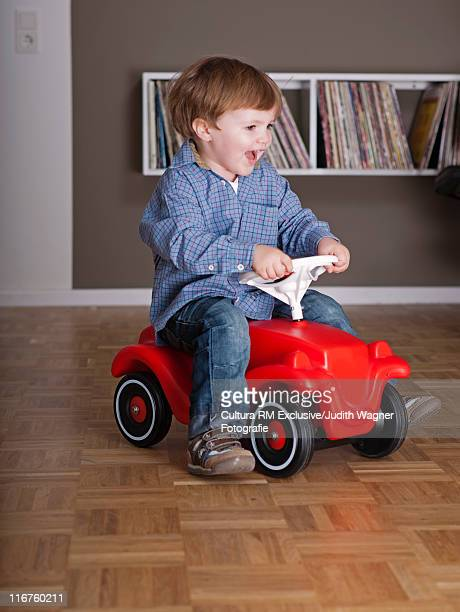 Boy riding toy car in living room