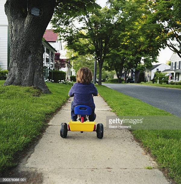 boy (3-5) riding tricycle on sidewalk, rear view - tricycle stock pictures, royalty-free photos & images