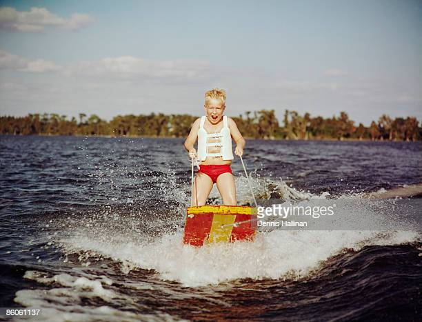 Boy riding water sled in lake