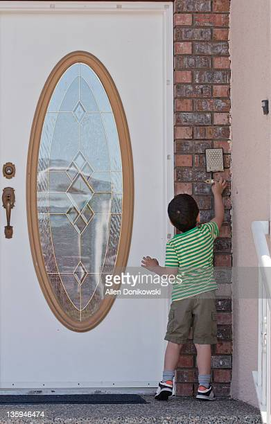 boy ringing doorbell - ringing doorbell stock pictures, royalty-free photos & images