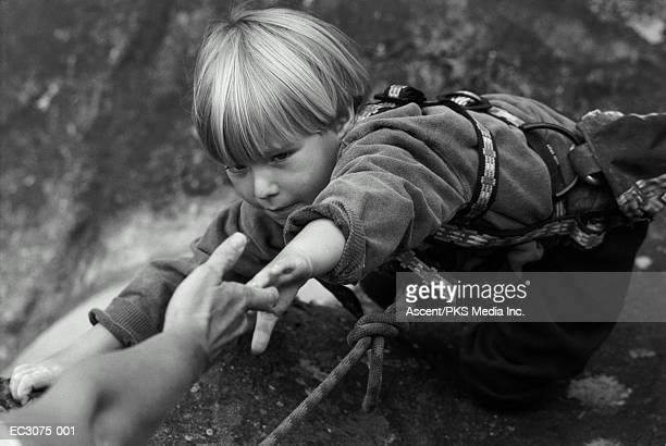 boy (4-6) rock climbing, extending hand to man above (b&w) - main noir et blanc photos et images de collection