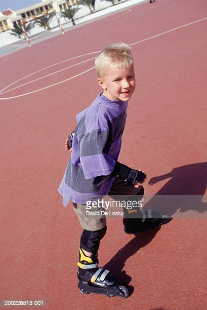 Boy (4-5) rollerblading on sports field