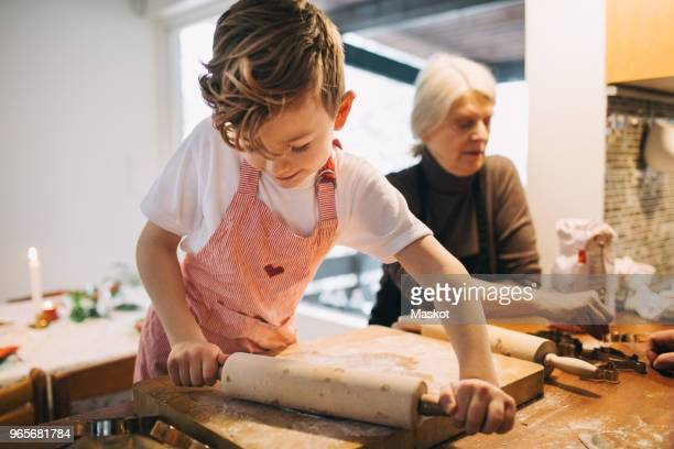boy rolling dough while standing by grandmother at kitchen counter - 焼いた ストックフォトと画像