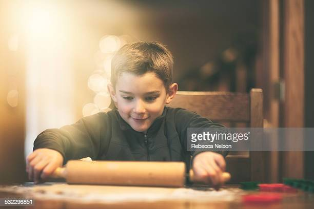 boy rolling out Christmas cookie dough