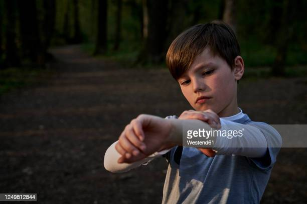 boy rolling sleeve while standing in forest - long sleeved stock pictures, royalty-free photos & images