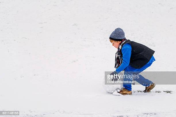 Boy rolling snow ball for making a snowman