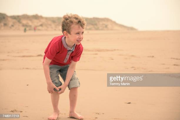 Boy rolling up his jeans on beach