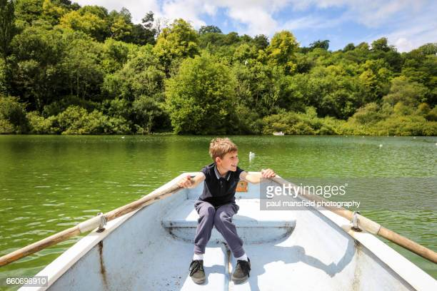 Boy rowing a boat by himself