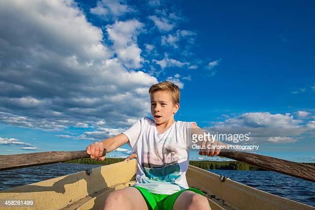 Boy rowing on lake