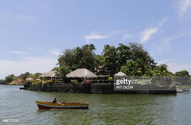 A boy rows a boat past an islet on Lake Nicaragua also known as the Cocibolca or Granada Lake in the Nicaraguan western city of Granada some 45Km...