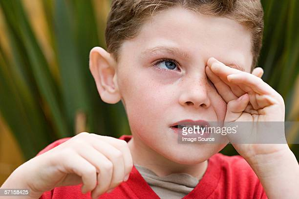 Boy rubbing his eye
