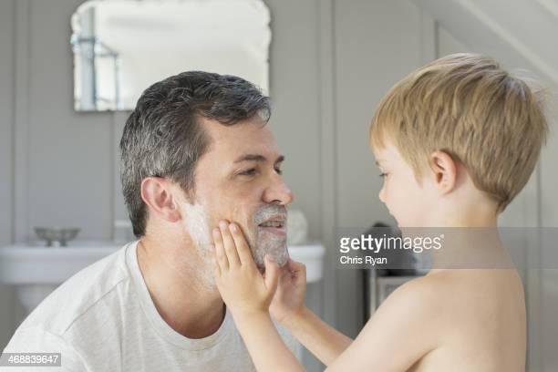 Boy rubbing shaving cream on father's face