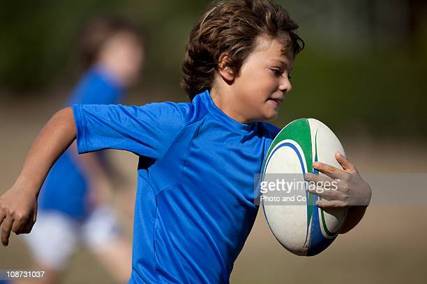 Boy rugby player running with ball