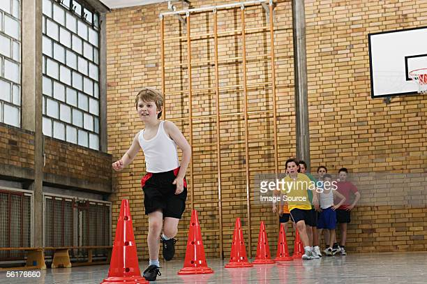 boy running a slalom race - physical education stock pictures, royalty-free photos & images
