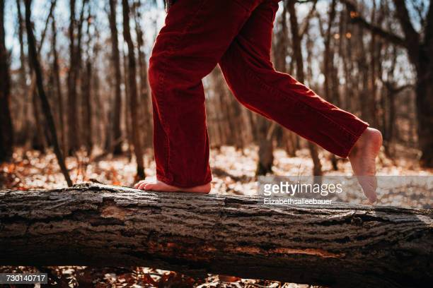 Boy running across a log barefoot