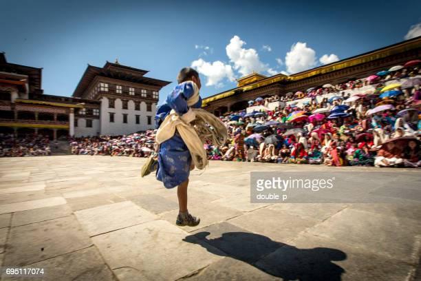 boy running across festival ground in Bhutan