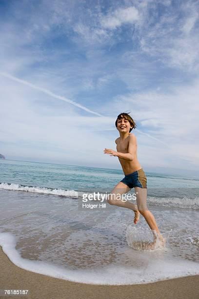 a boy running along a beach - jungen in badehose 12 jahre stock-fotos und bilder