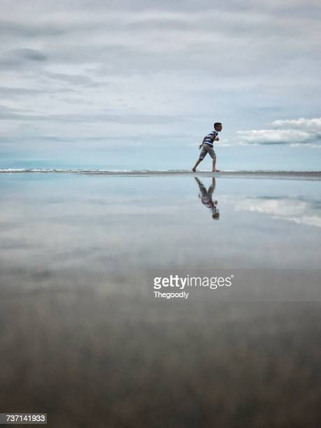 Boy running along beach